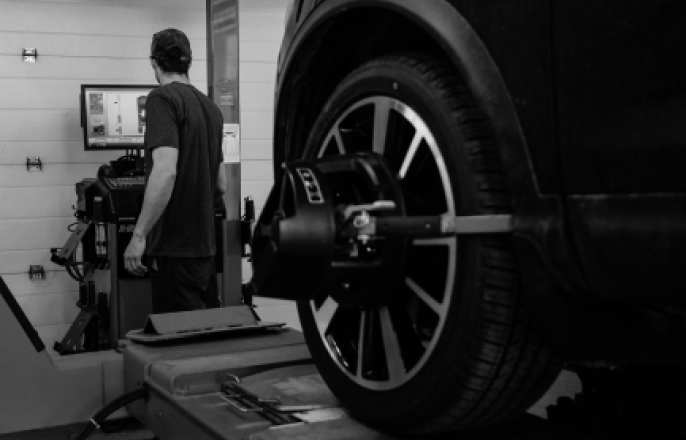 Auto Service Mechanic Checking Tires